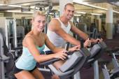 Fit young couple working on exercise bikes at gym — Stock Photo