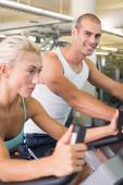 Fit young couple working on exercise bikes at gym — Foto Stock