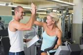 Trainer giving high five to his client on exercise bike at gym — Stock Photo