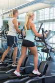 Fit young couple working on x-trainers at gym — Stock Photo