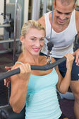 Male trainer assisting beautiful young woman on lat machine — Stock Photo