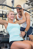 Male trainer assisting woman on a lat machine in gym — Stock Photo