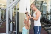 Trainer assisting young woman on a lat machine in gym — Stock Photo