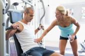 Trainer assisting man on fitness machine at gym — Stock Photo