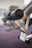 Fit woman using weights machine for legs — Stock Photo