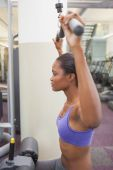 Fit woman using the weights machine for her arms  — Stock Photo