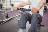 Fit man working out on rowing machine — Stock Photo
