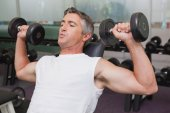 Fit man lifting dumbbells lying on the bench — Stock Photo