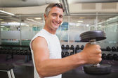 Fit man lifting heavy black dumbbell — Stock Photo