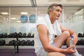 Fit man taking a break in the weights room — Stock Photo