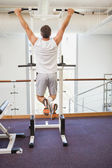 Fit man doing pull ups in fitness studio — Stock Photo