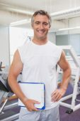 Fit personal trainer smiling at camera in fitness studio — Stock Photo