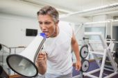 Angry personal trainer shouting through megaphone — Stock Photo