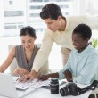 Casual business team looking at laptop together — Stock Photo #60661177