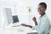 Happy businesswoman working at desk — Stock Photo