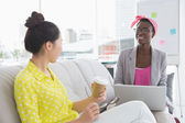 Young creative women chatting on the couch — Stock Photo