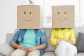 Young creative team wearing boxes on head — Stock Photo