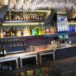 Close up on bar with wine glasses hanging above it — Stock Photo #60810481