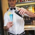 Handsome bartender serving blue cocktail — Stock Photo #60811571