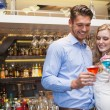 Cute couple standing and drinking cocktails — Stock Photo #60812363