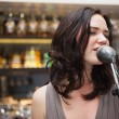 Brunette haired woman singing in a microphone — Stock Photo #60812857