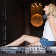 Sexy DJ girl with eyes closed sitting behind the decks — Stock Photo #60813031