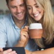 Cute couple using smartphone together — Stock Photo #60818489