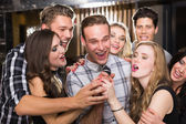 Happy friends singing karaoke together — Stock Photo