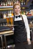 Pretty waitress holding a tray of champagne — Stock Photo