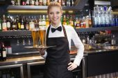 Waitress with hand on hip holding a tray of champagne — Stock Photo