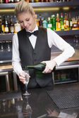 Cute woman in suit pouring champagne into flute — Stock Photo