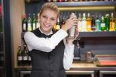 Pretty blonde waitress shaking cocktail — Stock Photo