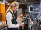 Barmaid pulling a glass of beer — Stock Photo