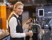 Barmaid pulling a glass of beer while looking at camera — Stock Photo