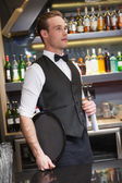Serious waiter holding tray and towel — Stockfoto