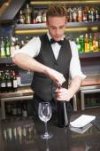 Handsome waiter opening a bottle of red wine — Foto Stock