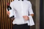 Handsome waiter holding a bottle of red wine and a towel — Stockfoto