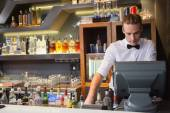 Handsome barman standing at the cash register — Stock Photo