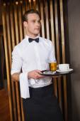 Smiling waiter holding tray with coffee cup and pint of beer — Stock Photo