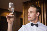 Handsome waiter inspecting a wine glass — Stock Photo