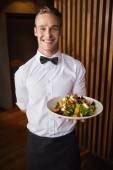 Smiling waiter showing plate of salad to camera — Foto Stock