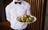 Waiter showing plate of salad to camera — Stock Photo