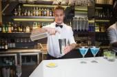 Smiling bartender preparing a drink at bar counter — Stockfoto