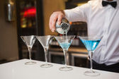 Bartender pouring blue alcohol into cocktail glass — Stock Photo