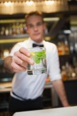 Happy bartender offering cocktail to camera — Foto Stock