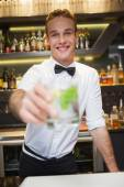 Happy bartender offering cocktail to camera — Stock Photo