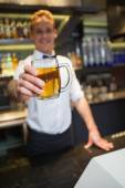 Smiling bartender offering pint of beer to camera — Foto Stock