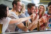 Happy friends holding cocktails into shot glasses — Foto de Stock