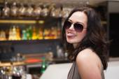 Pretty woman wearing sunglasses with tongue out — Stock Photo