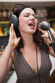 Woman singing with her hands on her headphone — Stock Photo